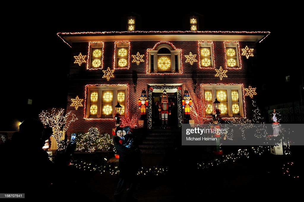 A woman holds a child as they pose for a photo in front of a decorated house on Christmas Eve December 24, 2012 in the Dyker Heights neighborhood of the Brooklyn borough of New York City. The neighborhood in the south part of the borough, is known for its yearly display of over the top holiday themed decorations.