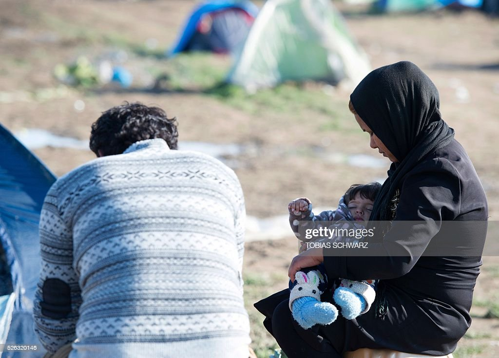 A woman holds a child at a makeshift camp for migrants and refugees near the village of Idomeni, not far from the Greek-Macedonian border, on April 30, 2016. Some 54,000 people, many of them fleeing the war in Syria, have been stranded on Greek territory since the closure of the migrant route through the Balkans in February. / AFP / TOBIAS