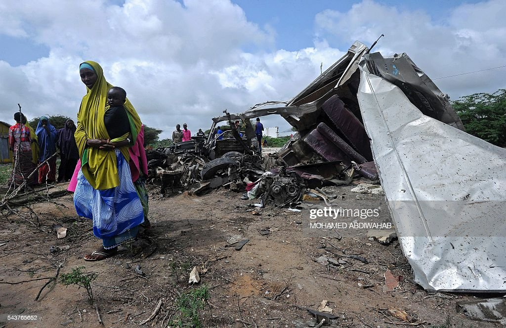 A woman holds a child near the explosion site of a minibus ripped apart by a landmine on June 30, 2016, in Afgooye. A roadside bomb ripped apart a minibus just outside Somalia's capital Mogadishu on Thursday, killing at least eight people and injuring several others, a witness said. 'There was a terrible incident, a landmine hit a civilian minibus,' said Mohamed Wedow, a witness at the scene near the town of Afgooye. 'At least eight people died and more than 20 others were wounded in the blast.' ABDIWAHAB