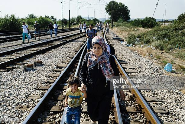 A woman holds a child's hand as a group of migrants walk on railway tracks towards the Macedonian town of Gevgelija from where they hope to catch a...