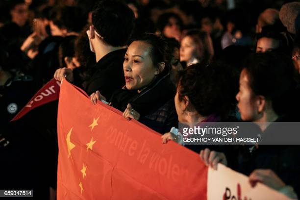 TOPSHOT A woman holds a Chinese flag during a protest in front of the police headquarters in the 19th arrondissement of Paris on March 28 following...