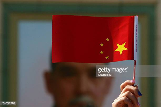 A woman holds a Chinese national flag infront of a giant portrait of Sun Yatsen the founder of modern China erected for the May Day at Tiananmen...