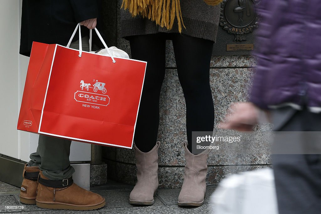 A woman holds a Coach Inc. shopping bag in the Ginza district of Tokyo, Japan, on Friday, Jan. 25, 2013. Japan's consumer prices fell for the seventh time in eight months, underscoring the risk that the central bank may struggle to reach a 2 percent inflation target unless it implements new easing measures earlier than planned. Photographer: Kiyoshi Ota/Bloomberg via Getty Images