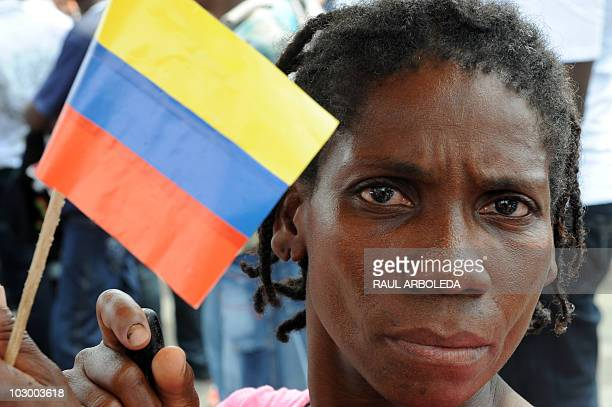 A woman holds a Colombian national flag as Colombian singer Juanes performs during the celebrations for the Bicentenary of the Independence of...