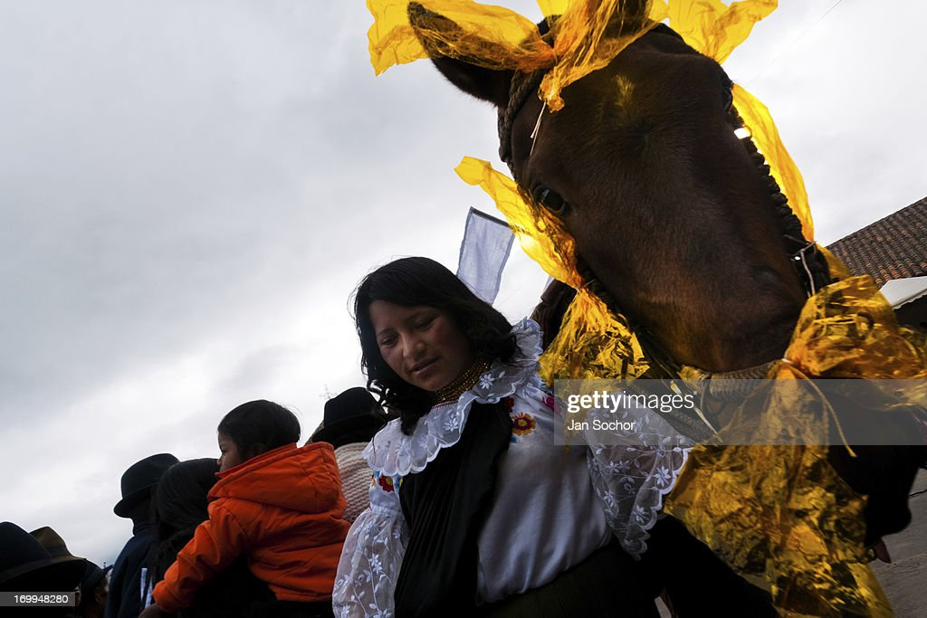 "A woman holds a colorfully decorated horse during the Inti Raymi celebration on 26 June 2010 in the village of Pesillo, Ecuador. Inti Raymi, ""Festival of the Sun"" in Quechua language, is an ancient spiritual ceremony held in the Indian regions of the Andes, mainly in Ecuador and Peru. The lively celebration, set by the winter solstice, goes on for various days. The highland Indians, wearing beautiful costumes, dance, drink and sing with no rest. Colorful processions in honor of the God Inti (Sun) pass through the mountain villages giving thanks for the harvest and expressing their deep relation to the Mother Earth (Pachamama)."