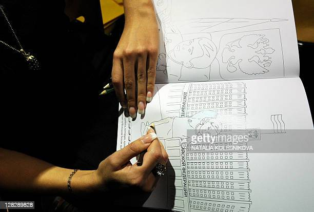 A woman holds a colouring book during a presentation in Moscow on October 6 2011 A Moscow publishing house has released a children's colouring book...