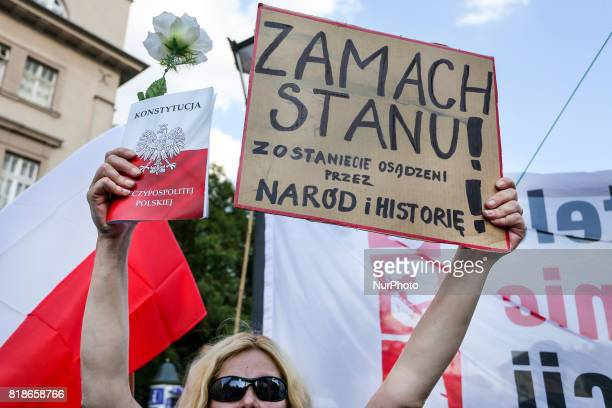A woman holds a copy of Polish constitution and a banner that says 'The Overthrow' during another day of protests against government plans for...