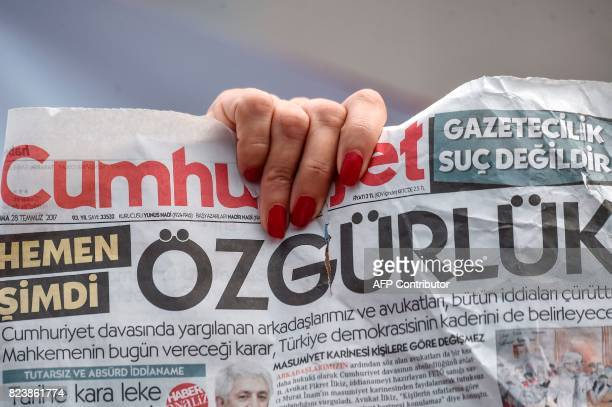 A woman holds a copy of today's Cumhuriyet daily newspaper with a word on the frontpage which can be translated as 'Freedom' on July 28 2017 during a...