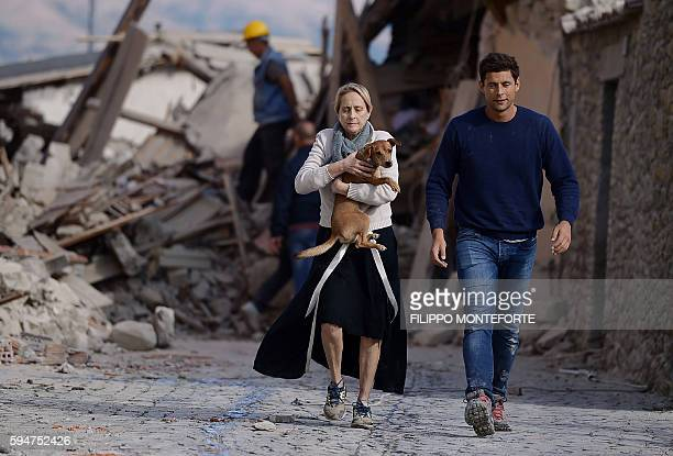TOPSHOT A woman holds a dog in her arms as she walks with a man next to the rubble of buildings in Amatrice on August 24 2016 after a powerful...
