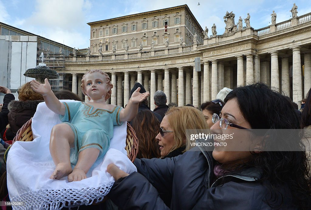 A woman holds a effigy of the infant Jesus to be blessed by Pope Benedict XVI during his weekly Angelus prayer on December 16, 2012 at the Vatican. The pontiff prayed for families of the victims in the Newtown, Connecticut, school massacre in the United States during his traditional weekly address to pilgrims on St Peter's Square. AFP PHOTO / VINCENZO PINTO