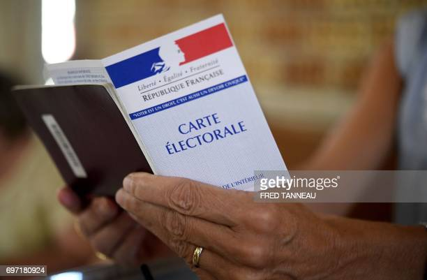 A woman holds a electoral card at a polling station in CarhaixPlouguer western France during the second round of the French parliamentary elections...