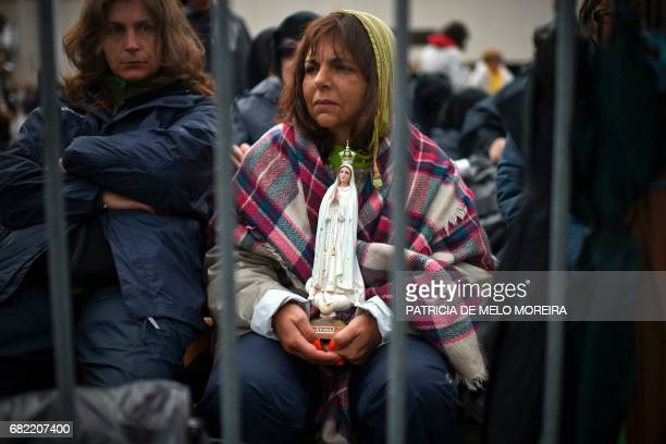 A woman holds a figure of Our Lady of Fatima as she waits for the arrival of Pope Francis at Fatima Sanctuary in Fatima central Portugal on May 12...
