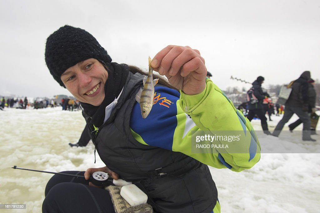 STORY - A woman holds a fish sitting on the frozen lake Viljandi, in Viljandi, Estonia during a ice fishing event on February 16, 2013. More than 8,000 participants from different countries arrived for the fishing event.