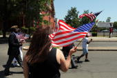 A woman holds a flag as veterans walk by while marching in a Memorial Day Parade on May 31 2010 in BridgeportConnecticut Bridgeport once home to...