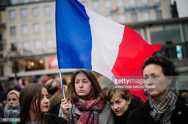 A woman holds a flag of France during a gathering in solidarity for France a day after deadly attacks in Paris on November 14 2015 in Stockholm Two...