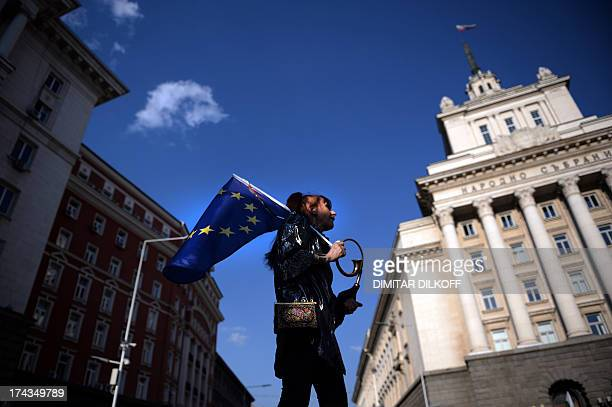 A woman holds a flag of the European Union during an antigovernment protest in Sofia on July 24 2013 Pressure mounted today for fresh elections in...