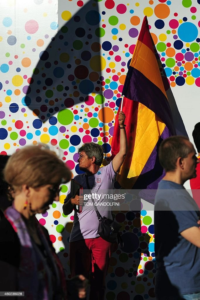 A woman holds a flag of the Spanish Second Republic during a demonstration to demand a referendum on the monarchy following the abdication of King Juan Carlos, in Madrid on June 7, 2014. Dozens of left-wing political parties and citizens organisations came together to demand 'A referendum now!' on the future of the monarchy. Spanish King Juan Carlos' abdication on June 2 revived anti-royalist fervour in the young democracy, sending thousands into the streets clamouring for a referendum on the monarchy itself.
