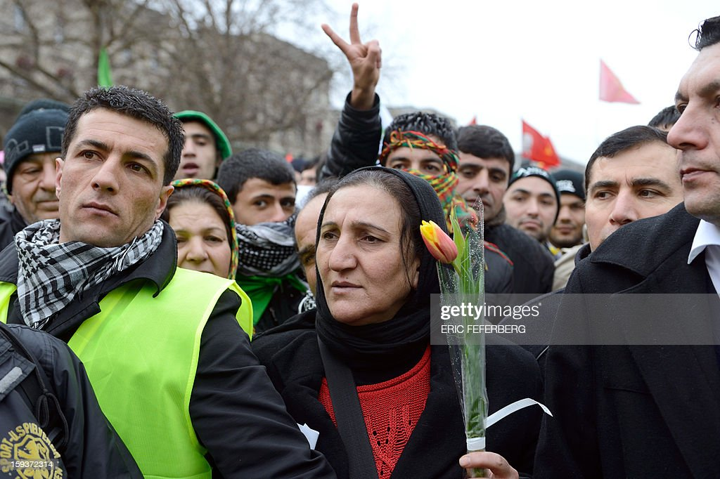 A woman holds a flower as she takes part in a demonstration with hundreds of people of Kurdish origin, on January 12, 2013 in Paris, two days after three Kurdish women were found shot dead at Paris Kurdistan Information Bureau. Thousands of Kurds from all over Europe are gathered in Paris today for what is expected to be an angry protest over the killing of three female activists shot dead at least three times in the head, giving further credence to the theory of an execution-style hit. Kurdish activists have accused Turkey or rogue nationalist elements in the country's military of being behind the killings. AFP PHOTO /ERIC FEFERBERG