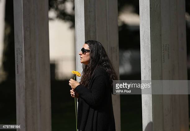 A woman holds a flower during a service at the July 7 memorial in Hyde Park to commemorate the tenth anniversary of the London 7/7 bombings on July 7...