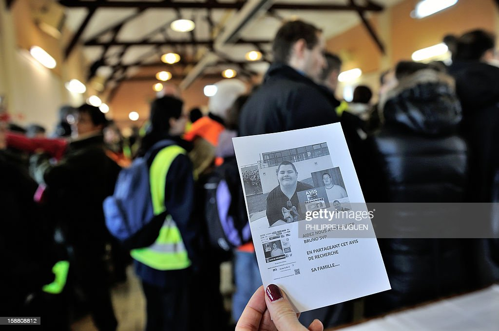 A woman holds a flyer with pictures of Bruno, a young trisomic man reported missing since December 18 before to take part in searches to find him on December 30, 2012 in Pimprez.