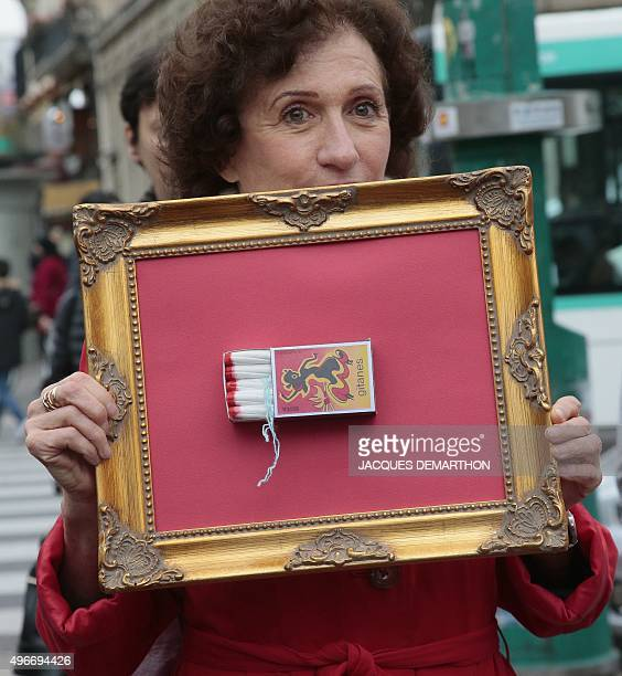 A woman holds a frame with a 'Gitanes' matchbox full of tampons during a demonstration in Paris on November 11 calling for reduced taxes on tampons...