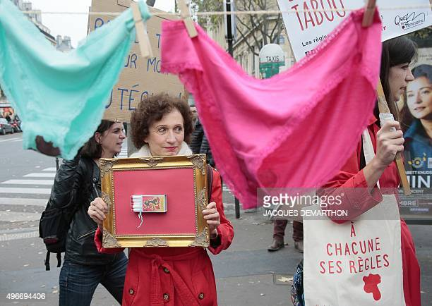 A woman holds a frame with a matchbox full of tampons during a demonstration in Paris on November 11 calling for reduced taxes on tampons and women's...