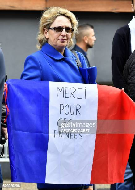 A woman holds a French flag reading 'Thanks for these years' as outgoing French President Francois Hollande visits polling stations after casting his...