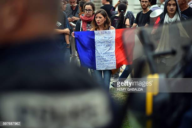 A woman holds a French national flag as she stands in front of French Policemen during a protest against the Labour law reform organised by French...