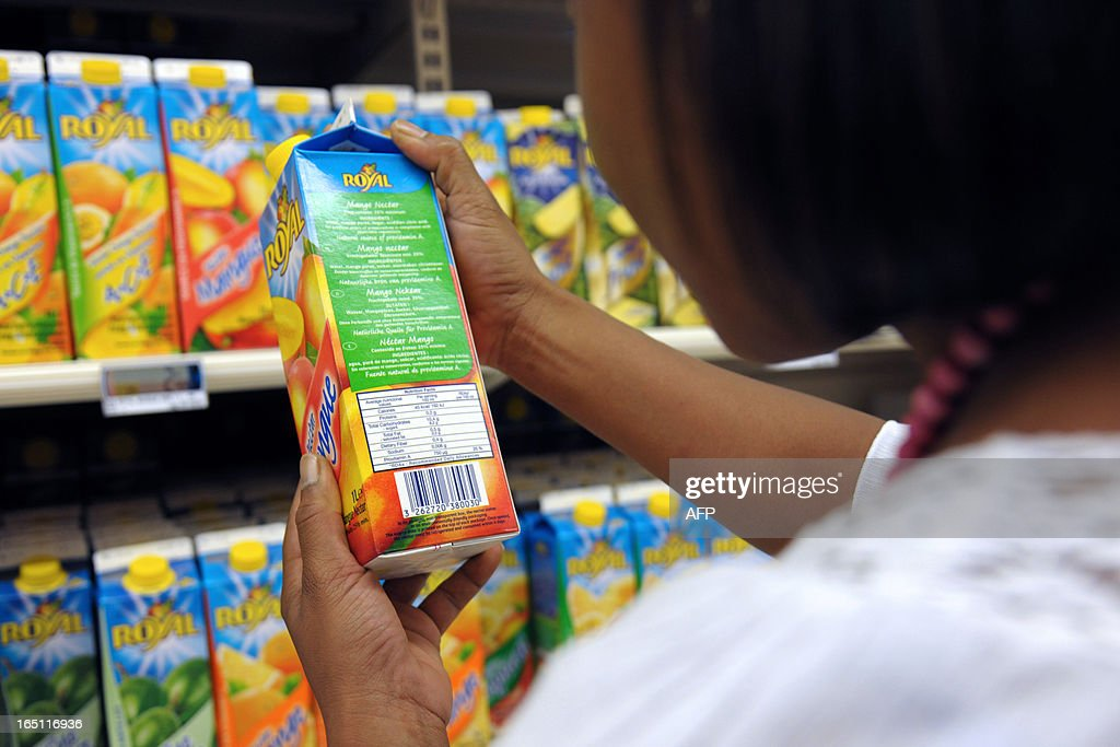 A woman holds a fruit juice bottle in a supermarket of Fort-de-France, on March 30, 2013 in the French caribean island of La Martinique. The French national assembly on March 27, 2013 ruled to align the additional sugar rates of the products sale in the overseas territories with the mainland's rates.
