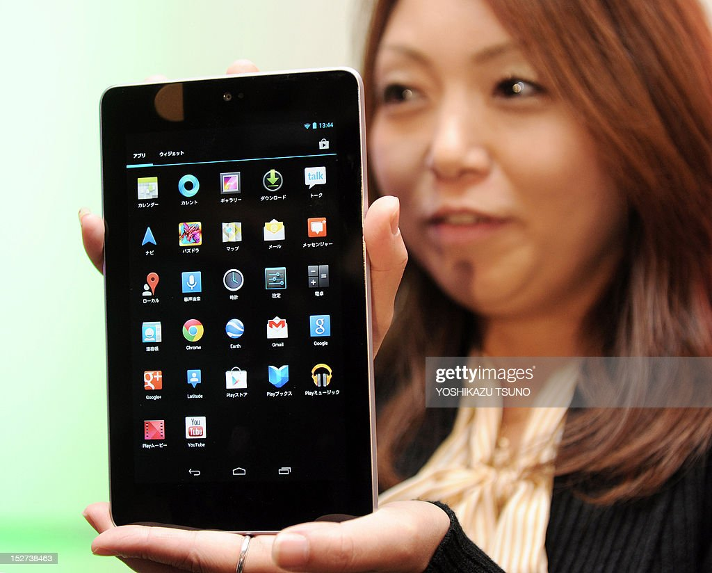 A woman holds a Google Nexus 7 tablet computer equipped with a 7-inch LCD display and a quad-core Tegra processor in its 340g body in Tokyo on September 25, 2012. Google said on September 25 it was launching its Nexus 7 tablet computer in Japan, aiming to take on Apple's iPad in one of the most lucrative markets in the world. AFP PHOTO / Yoshikazu TSUNO
