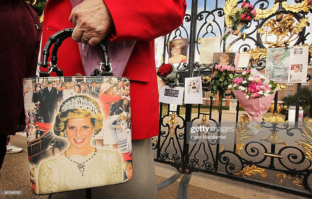 A woman holds a handbag with a picture Diana, Princess of Wales in front of the gates of Kensington Palace on August 31, 2009 in London, England. Fans gathered to remember Diana, Princess of Wales who died in a Paris car crash 12 years ago today.