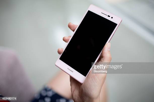 A woman holds a Huawei Technologies Co Ascend P7 smartphone for a photograph inside an exhibition hall at the company's campus in the Longgang...