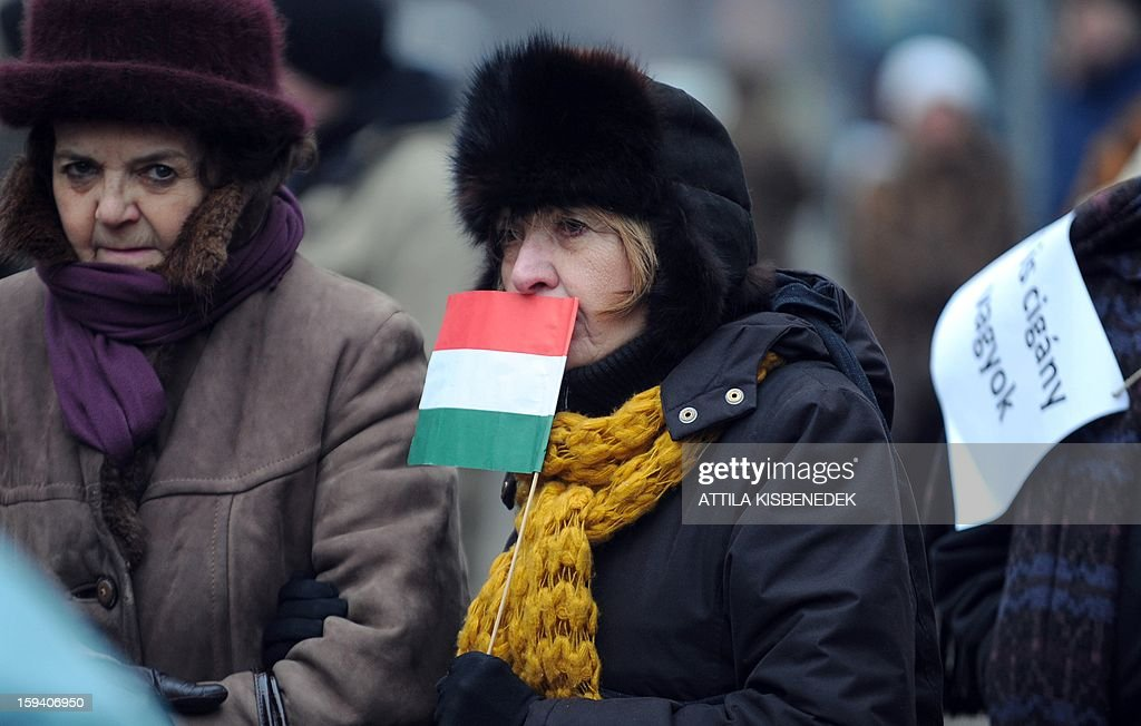 A woman holds a Hungarian flag during a demonstration organized by a small leftist parliament party, the Democratic Coalition (DK), against racism, segregation, and hate speech in connection with a recent, anti-Roma article by journalist Zsolt Bayeran, on January 13, 2013 in Budapest. Several hundred members and supporters of the party, including DK head Ferenc Gyurcsany and Socialist politicians, gathered in front of the headquarters of the ruling Fidesz party, of which Bayer is a member. In an article published last weekend, Bayer commented on a recent stabbing involving Roma suspects, and wrote that 'a significant number of Gypsies are unsuitable for co-existence [...] These Gypsies are animals and act as animals [...] they should not be tolerated or understood but punished.' AFP PHOTO / ATTILA KISBENEDEK