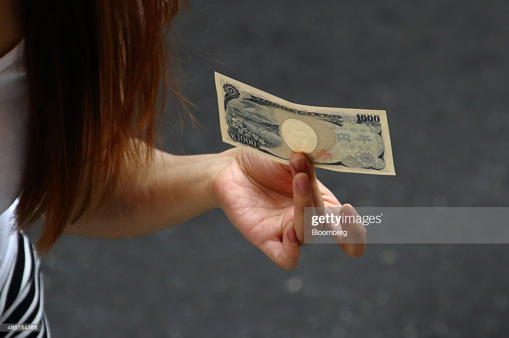 A woman holds a Japanese 1000 yen banknote as she shops at a store in Tokyo Japan on Tuesday Aug 25 2015 The yen fell against the dollar for the...