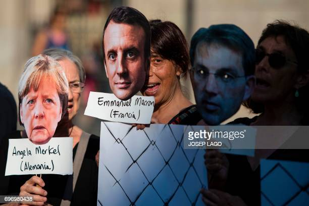 A woman holds a mask with the face of French President Emmanuel Macron between two other women holding masks of German Chancellor Angela Merkel and...