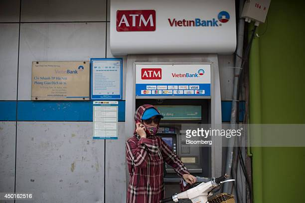 A woman holds a mobile phone in front of a Vietnam Joint Stock Commercial Bank For Industry and Trade automated teller machine in Hanoi Vietnam on...