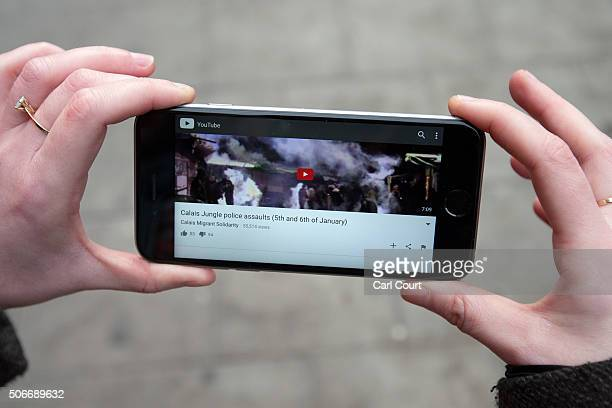 A woman holds a mobile phone showing the video that is linked from a QR code on a Banksy artwork opposite the French embassy on January 25 2016 in...