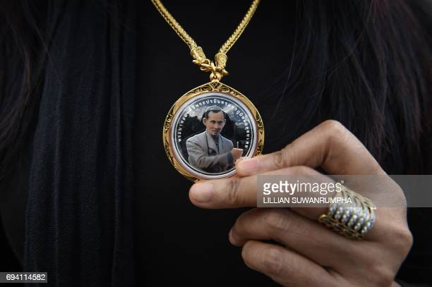 A woman holds a necklace with the image of the late Thai King Bhumibol Adulyadej in Bangkok on June 9 2017 / AFP PHOTO / LILLIAN SUWANRUMPHA
