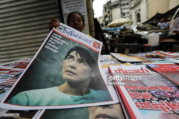 A woman holds a newspaper featuring a photograph of opposition leader leader Aung San Suu Kyi at a stall in Yangon Myanmar on Monday Nov 9 2015 The...