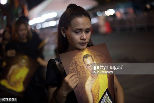 A woman holds a painted portrait of Thailand's late king as she and others leave the Grand Palace in Bangkok on October 5 after mourning him in the...