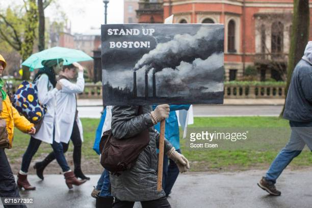 A woman holds a painted sign while marching from MIT to the Boston Common for the Science March on April 22 2017 in Boston Massachusetts The event is...
