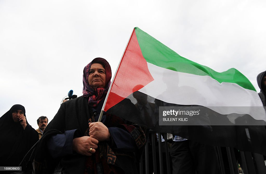 A woman holds a Palestinian flag as protesters gathered in front of the courtroom, on November 6, 2012, in Istanbul. Four Israeli ex-military chiefs went on trial in absentia in an Istanbul court over a deadly 2010 raid on a Gaza-bound Turkish ship in what Israel branded a 'show trial' by its former ally.Prosecutors are seeking life sentences for the four over the night-time assault in international waters in the Mediterranean Sea that plunged relations between Israel and Turkey into deep crisis.