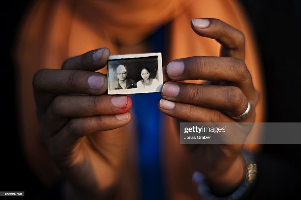A woman holds a passport photo of lost daughter An image A name A memory A photograph is often the only thing families have left of their lost...