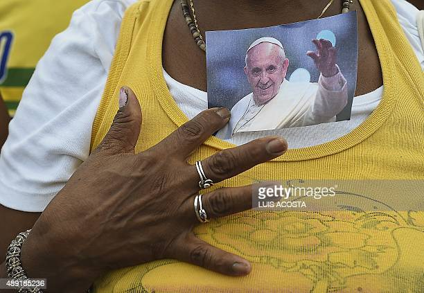 A woman holds a photo of Pope Francis during his visit in Havana on September 19 on the first leg of a highprofile trip that will also take him to...