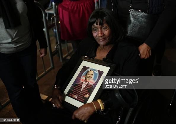 A woman holds a photo of President Barack Obama before he gives his farewell address in Chicago Illinois on January 10 2017 Barack Obama closes the...