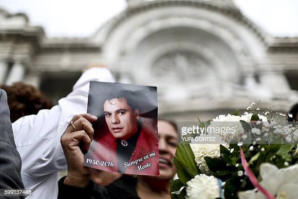 A woman holds a photo of the late Mexican singersongwriter in front of the Fine Arts Palace in Mexico City on September 4 2016 while waiting for the...