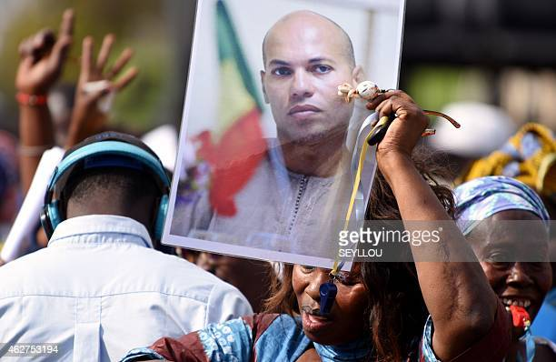 A woman holds a picture of Karim Wade former minister and son of former Senegalese president Abdoulaye Wade during a meeting of the opposition on...