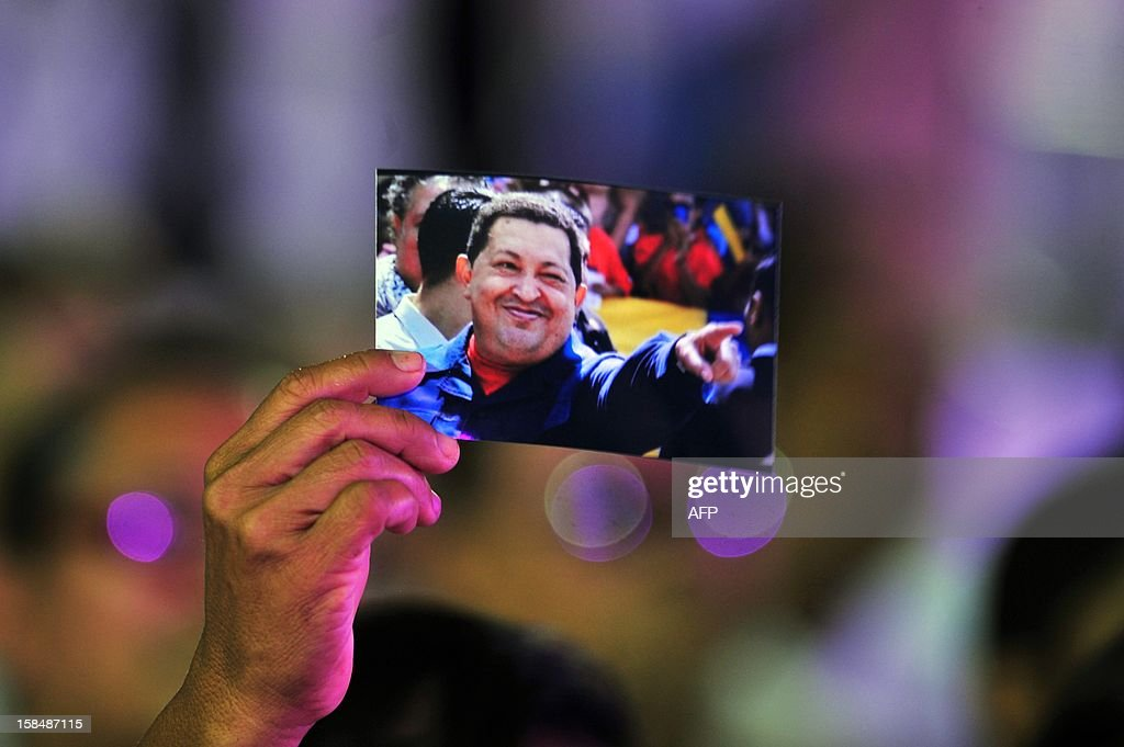 A woman holds a picture of Venezuelan President Hugo Chavez during the concert 'Song, Life and Hope, celebrated in his honor, December 17, 2012 in Managua. Chavez is recovering in Cuba following a fourth operation for a recurrence of cancer. AFP PHOTO/Hector RETAMAL