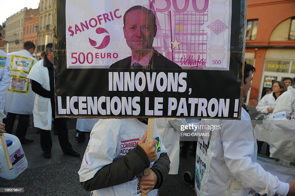 A woman holds a placard against pharmaceutical group Sanofi during a demonstration called by unions, as part an European day of protest against austerity, on November 14, 2012 in Toulouse. General strikes in Spain and Portugal will spearhead the day of action called by European unions and joined by activists as anger over governments' tight-fisted policies boils over.