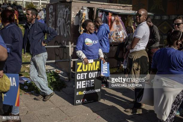 A woman holds a placard as opposition parties members march to support a Motion of no Confidence against South African president Jacob Zuma to be...